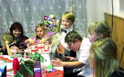 Děti zDětského domova Sázava si rozbalují své vánoční dárky